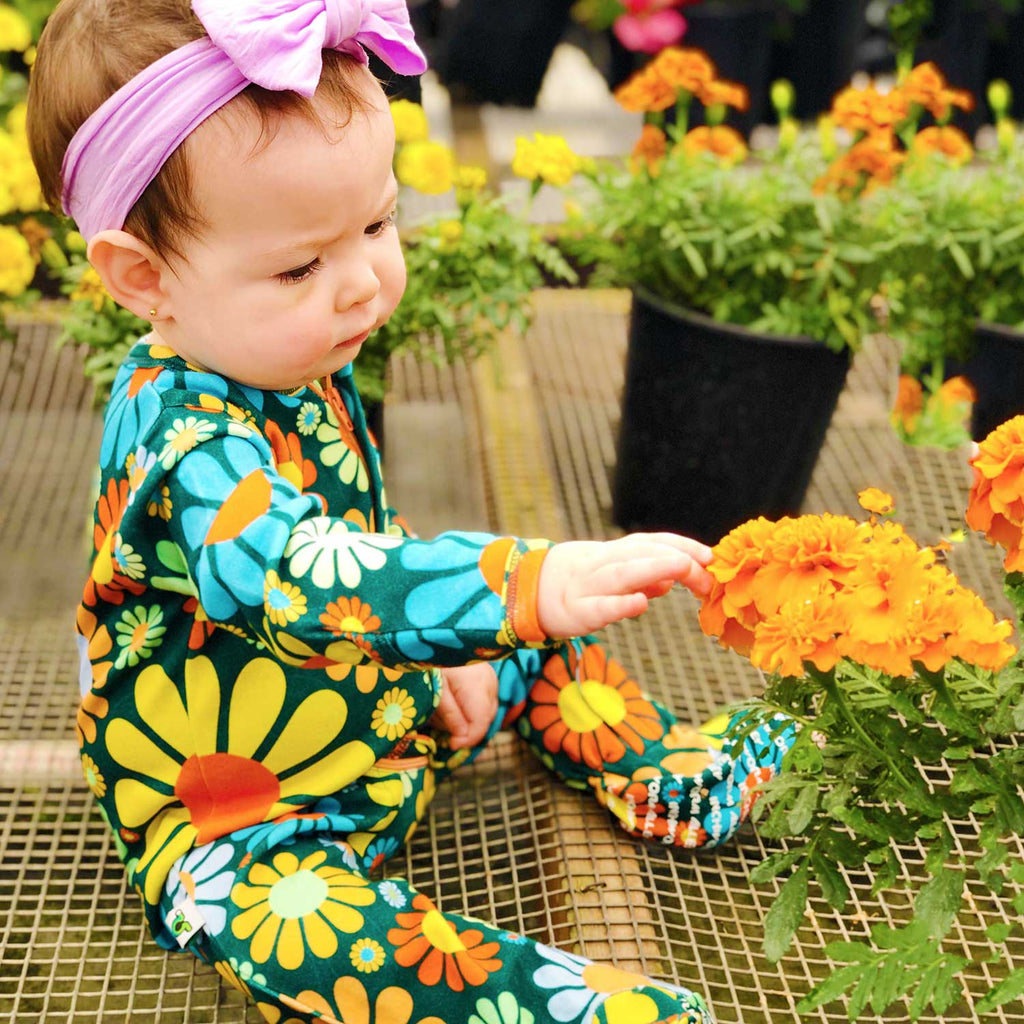 Baby wearing a long sleeve footie with an all-over print of 70s inspired flowers
