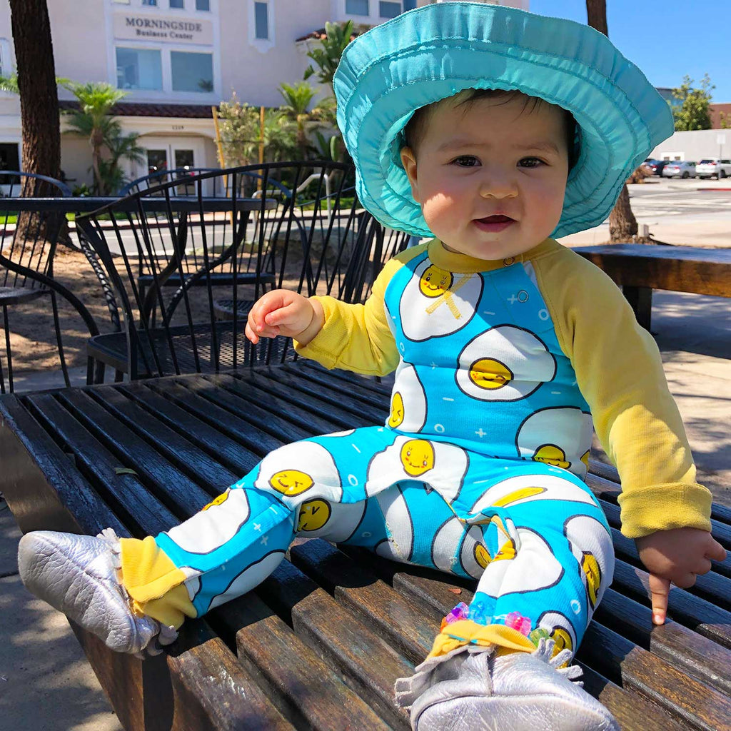 Baby wearing a full sleeve raglan romper with cartoon print of cute and kawaii fried eggs