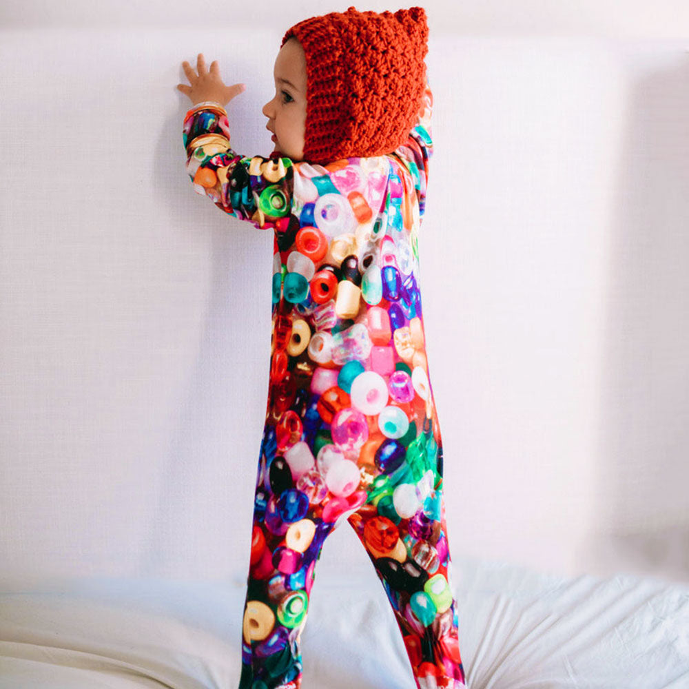 Baby wearing a long sleeve footie with an all-over print of multicolor beads
