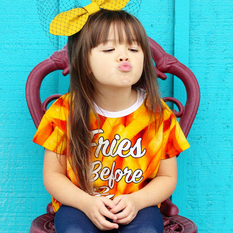 Girl wearing a boxy tee with all-over print of french fries and the words Fries Before Guys across the chest