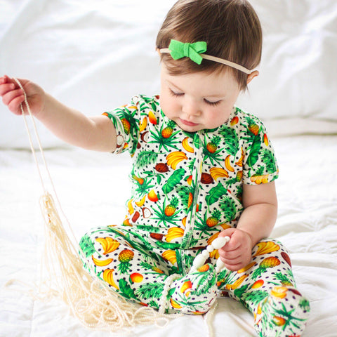 Baby wearing a short sleeve footie printed with palm leaves, coconuts, bananas, pineapples and mangoes
