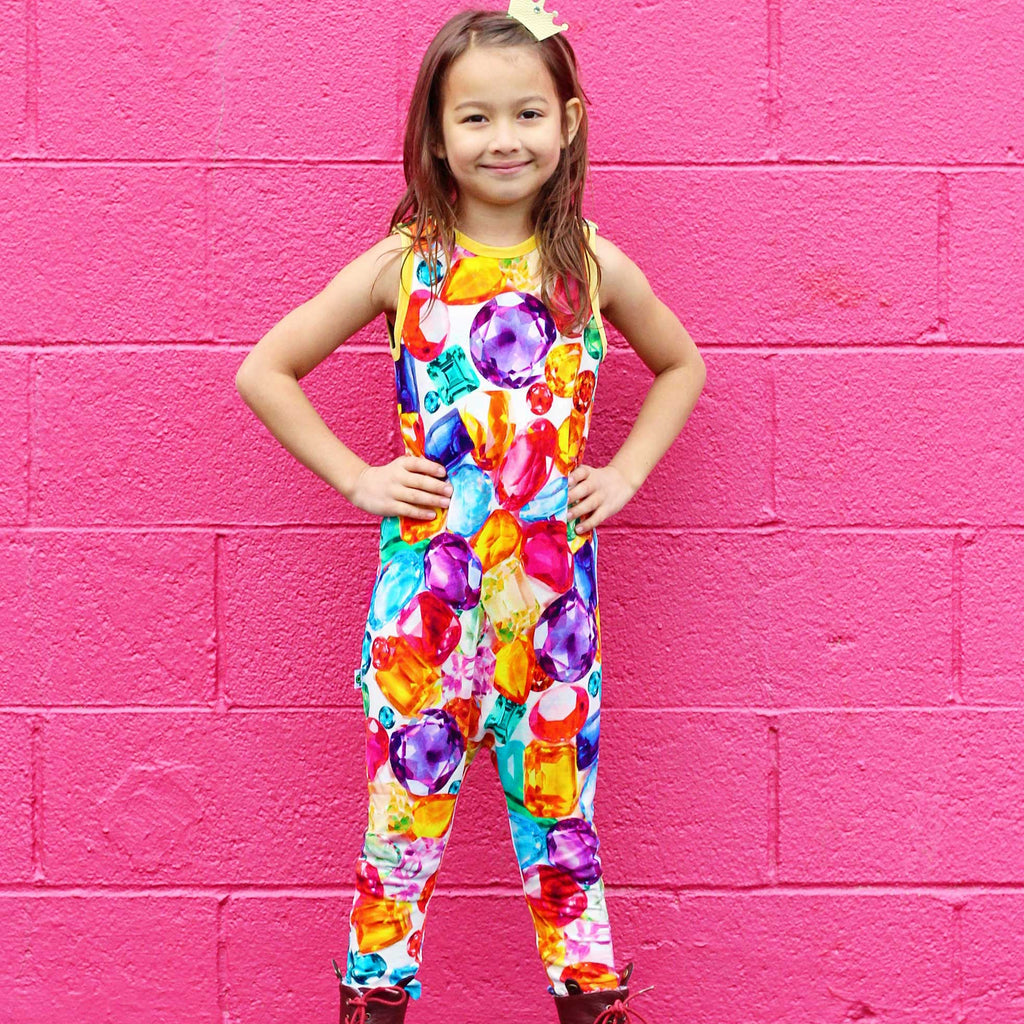Child wearing a tank jumpsuit with image of oversized, scattered precious gemstones