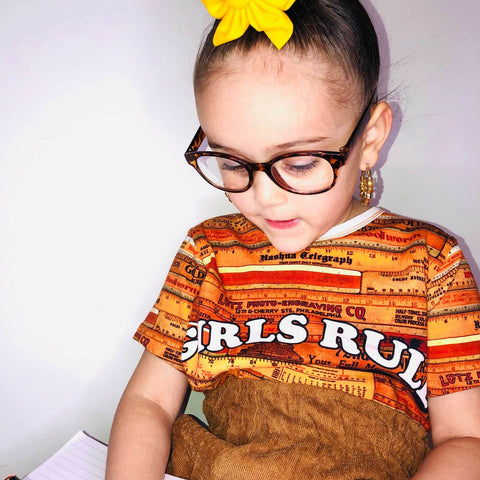 Girl wearing a graphic tee with an all-over print of wooden school rulers and the words Girls Rule across the chest