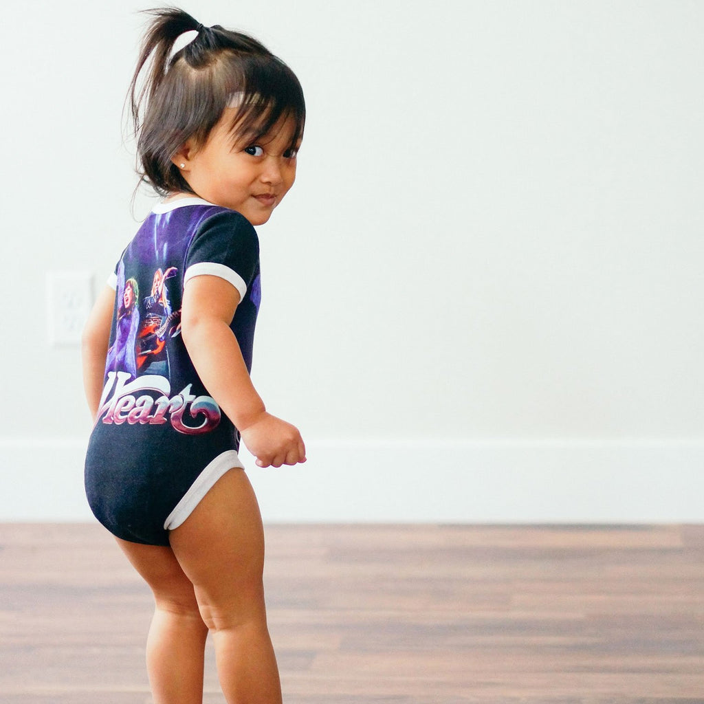 Toddler wearing a sleeve bodysuit onesie printed with an image of the band Heart