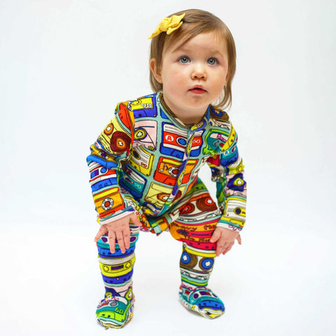 Baby wearing a long sleeve footie with an all-over print of hand drawn cassette tapes