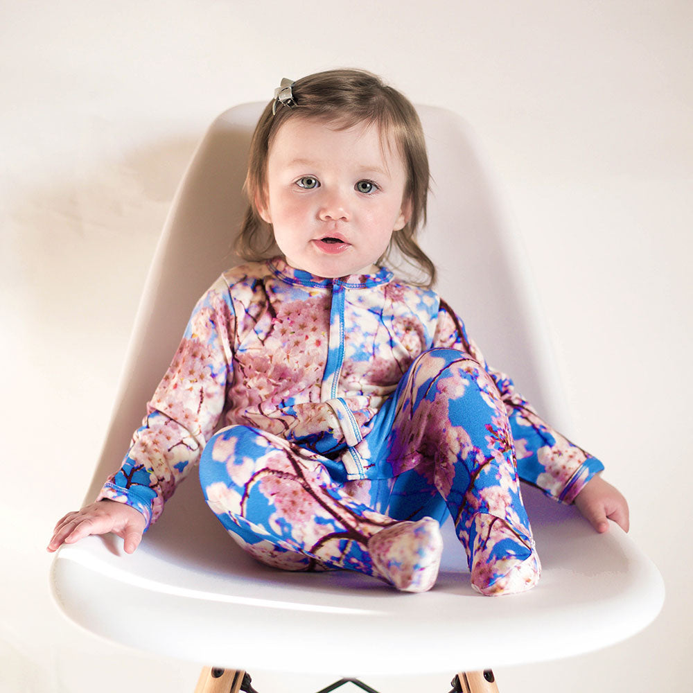 Baby wearing a long sleeve footie with an all-over print of cherry blossoms