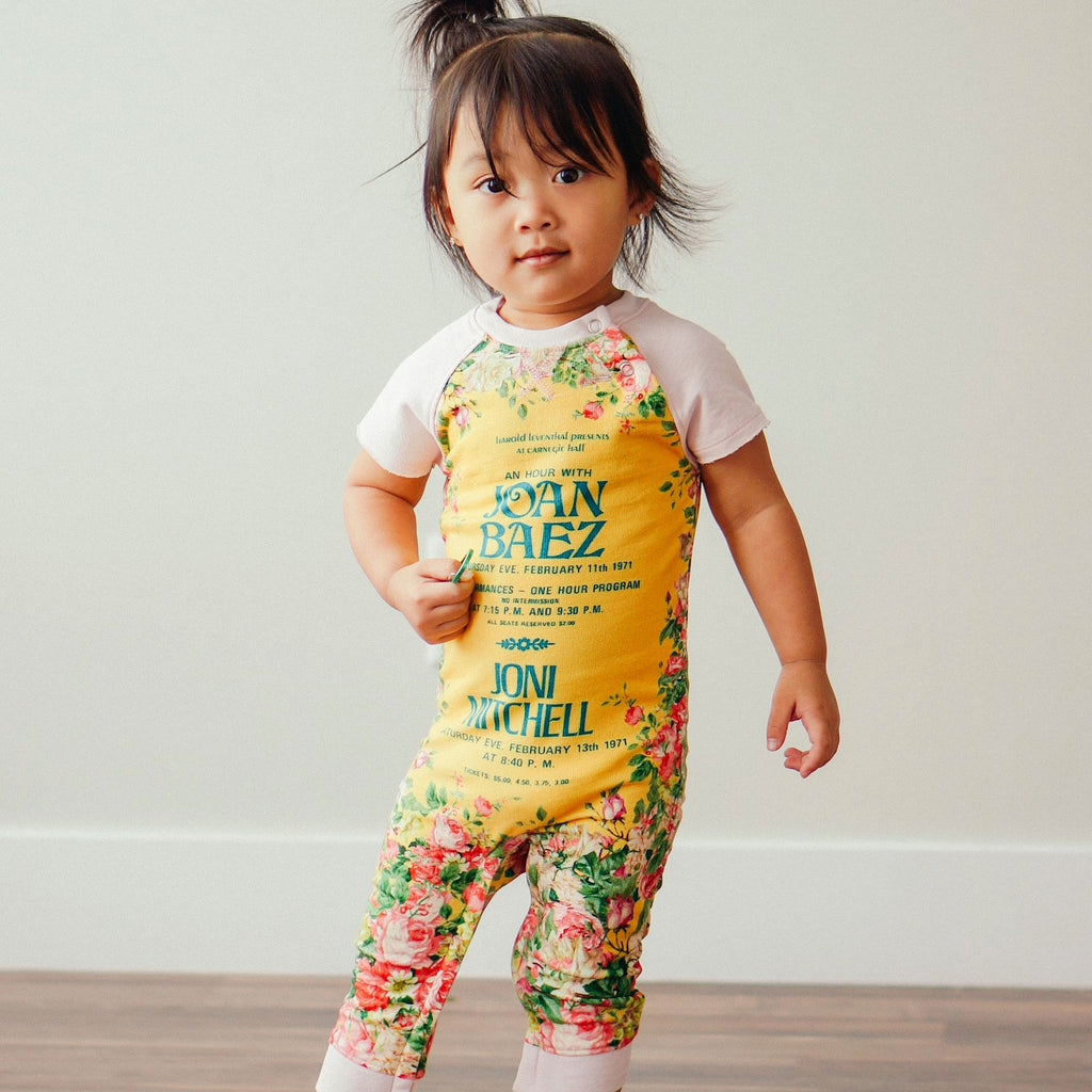 Toddler wearing a raglan cut-off romper printed with a vintage concert poster for Joan Baez and Joni Mitchell surrounded by pink flowers