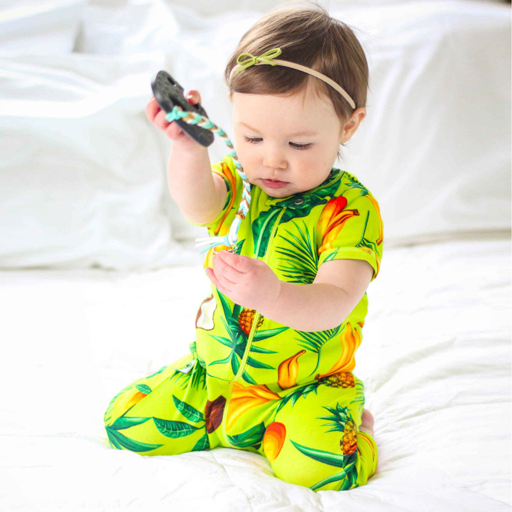 Baby wearing short sleeve, full leg romper with an all-over print of pineapples, coconuts, bananas, mangos and palm fronds