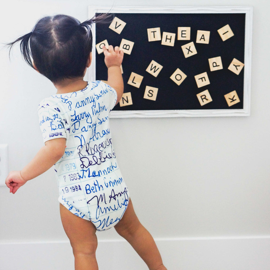 Baby wearing a short sleeve bodysuit onesie printed with a large-scale image of a retro library card intended for signing out books