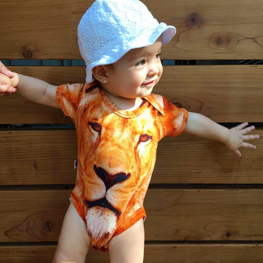 Toddler wearing a short sleeve bodysuit printed with a portrait of a lion