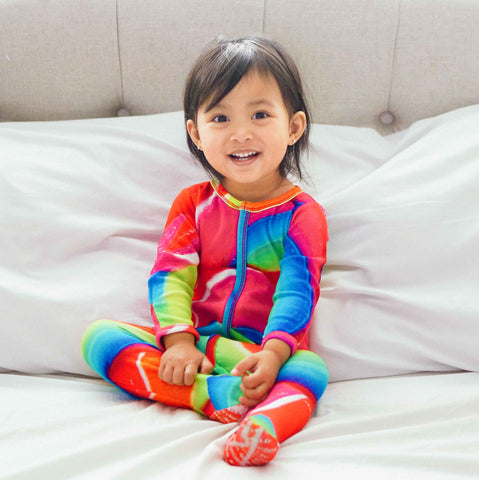 Toddler wearing a long sleeve footie with zoomed in image of a multicoloured rainbow lollipop swirl