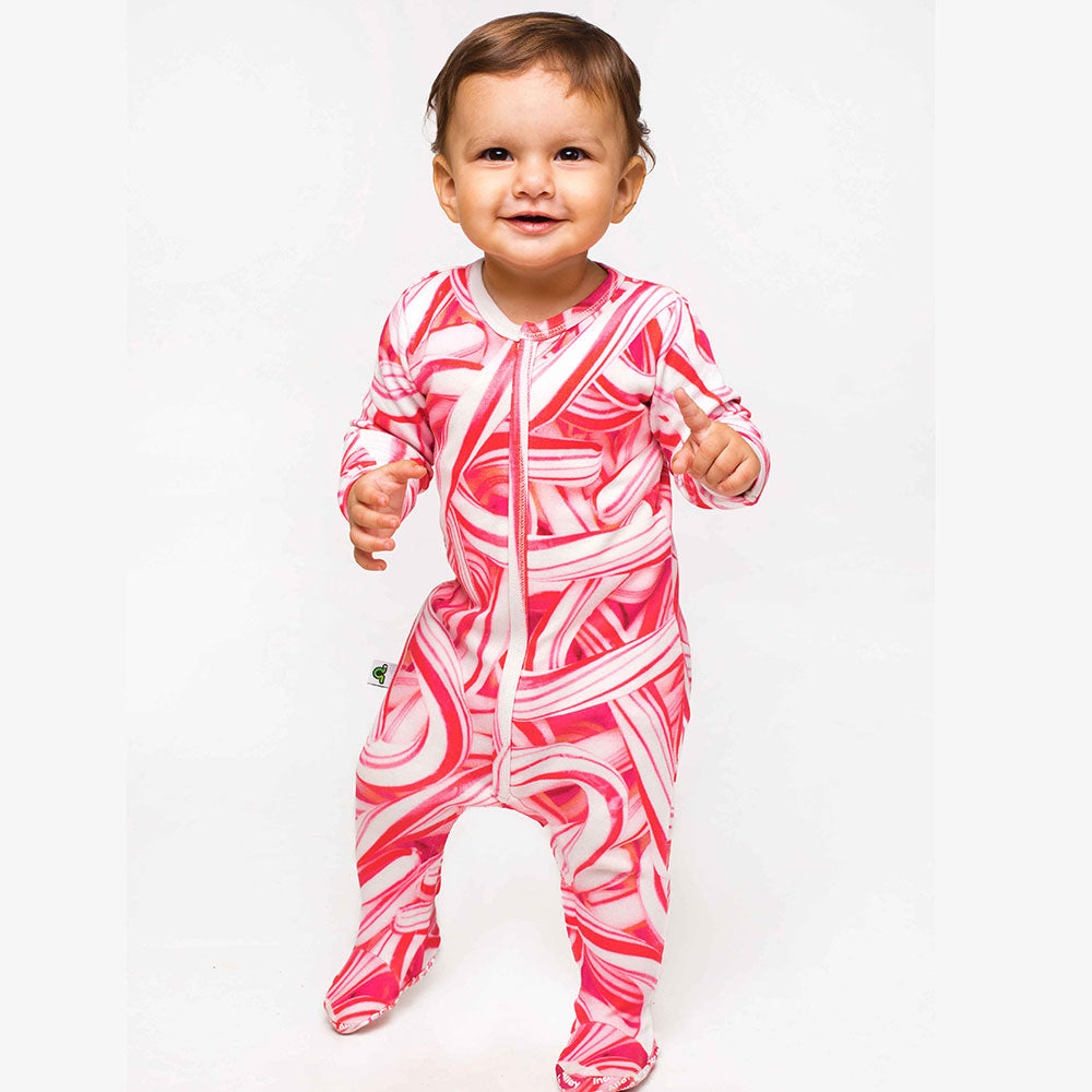 Baby wearing a long sleeve footie with all-over print of red and white candy canes