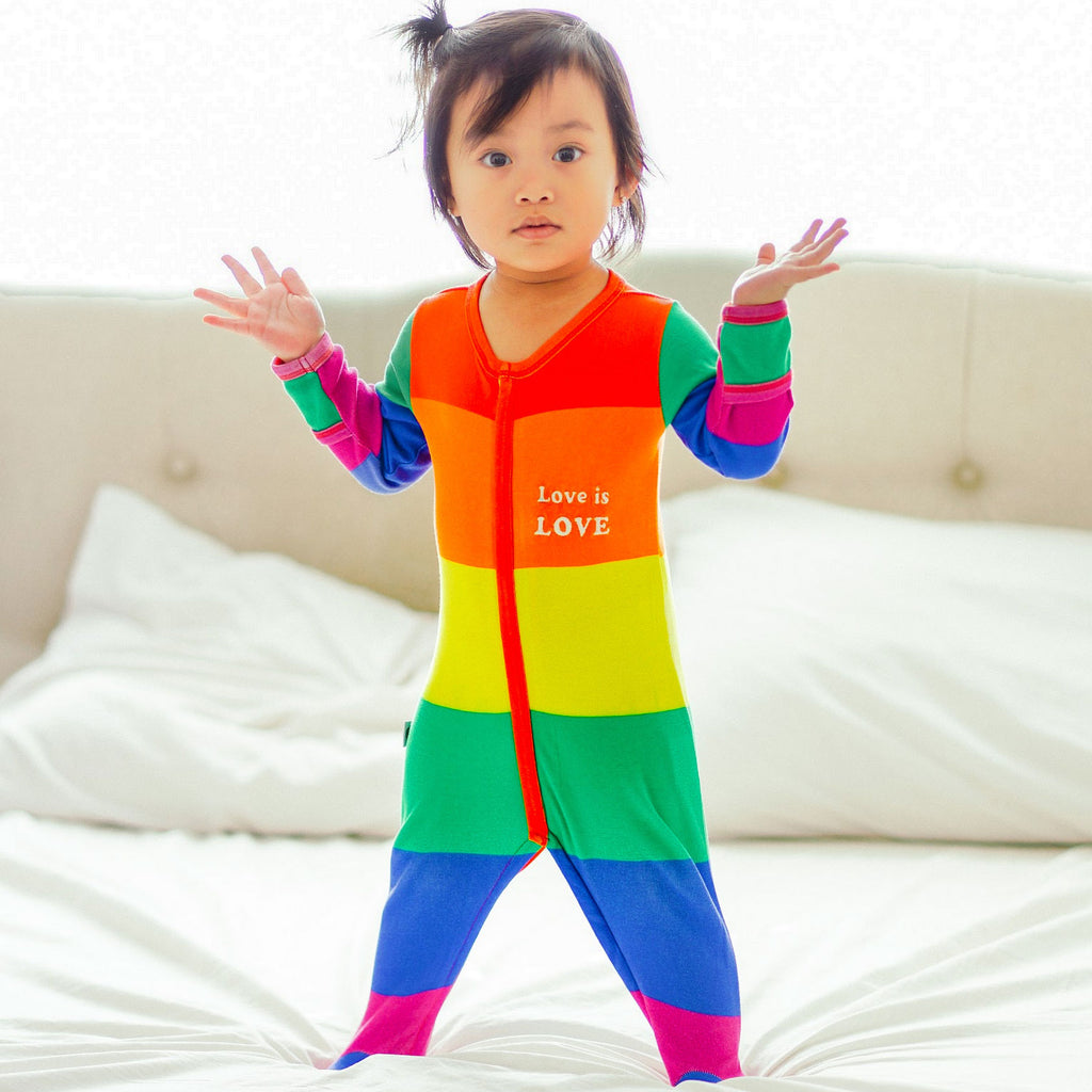 Baby wearing a long sleeve footie in LGBTQ rainbow flag print with the words Love Is Love on left chest