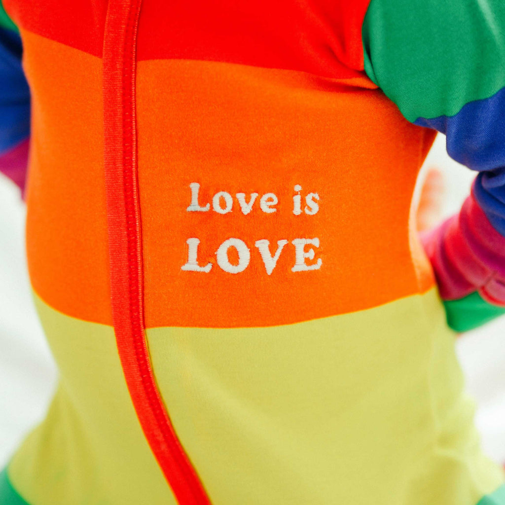 Close up of a long sleeve footie in LGBTQ rainbow flag print with the words Love Is Love on left chest