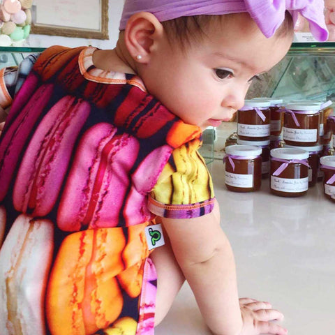 Baby wearing a short sleeve bodysuit printed with an image of rows of colourful macarons
