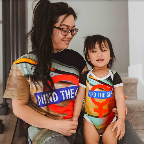 "Mother and daughter wearing matching outifts with an image of the London underground subway superimposed with ""Mind The Gap"" and the symbol for female"