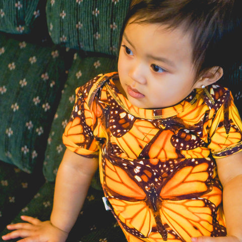 Baby wearing short sleeve bodysuit onesie with an all-over print of a collage of monarch butterflies