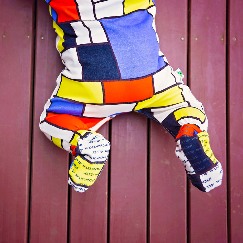 "Baby wearing a short sleeve footie with all over print of Piet Mondrian's ""Composition II in Red, Blue, and Yellow"""