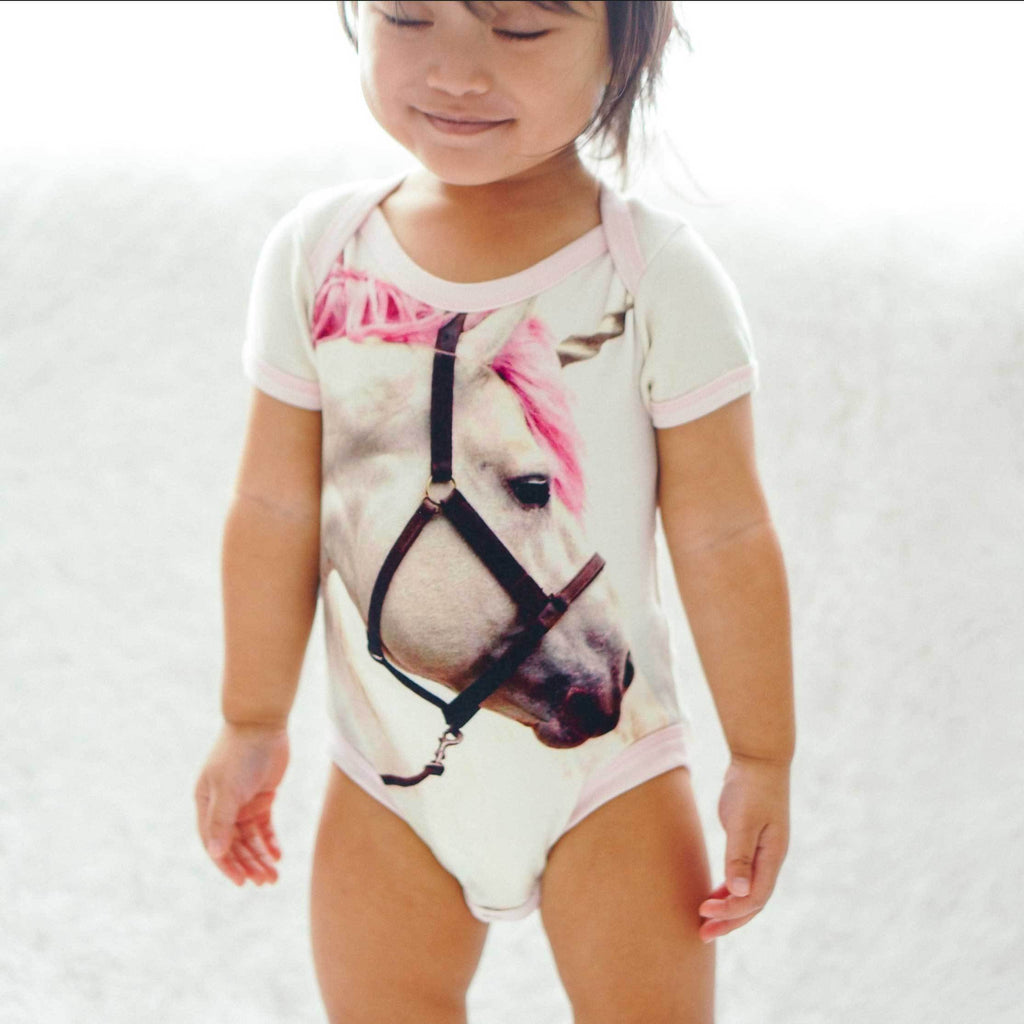 Baby wearing a short sleeve bodysuit onesie with a print of a dreamy white unicorn with a pink mane