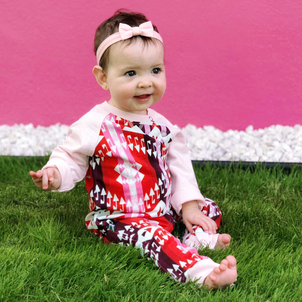 Baby wearing a full sleeve raglan romper with Navajo-inspired design in bright hues of red and pink.
