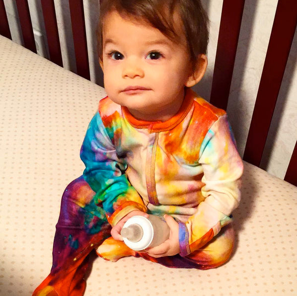 Baby wearing a long sleeve footie with a stylized image of the Orion Nebula
