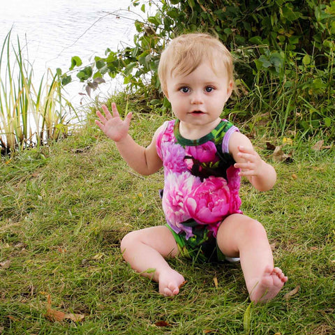 Baby wearing a tank bodysuit printed with pink peonies