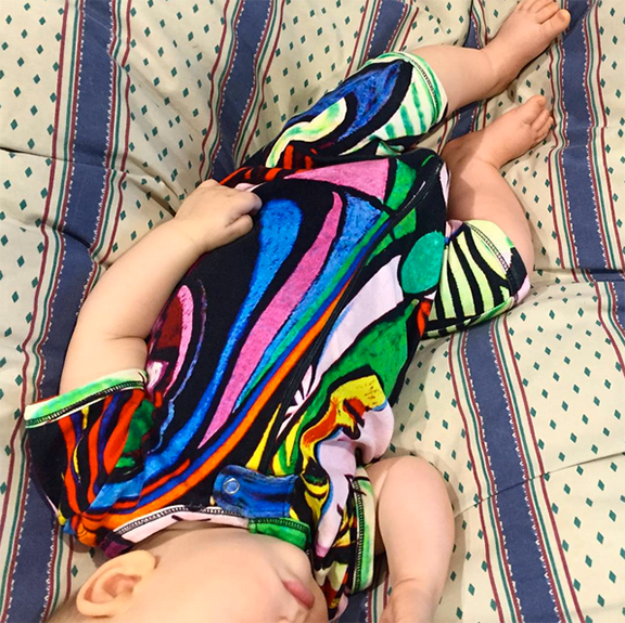 "Baby wearing a short sleeve romper with shorts printed with Picasso's ""Girl Before A Mirror"""