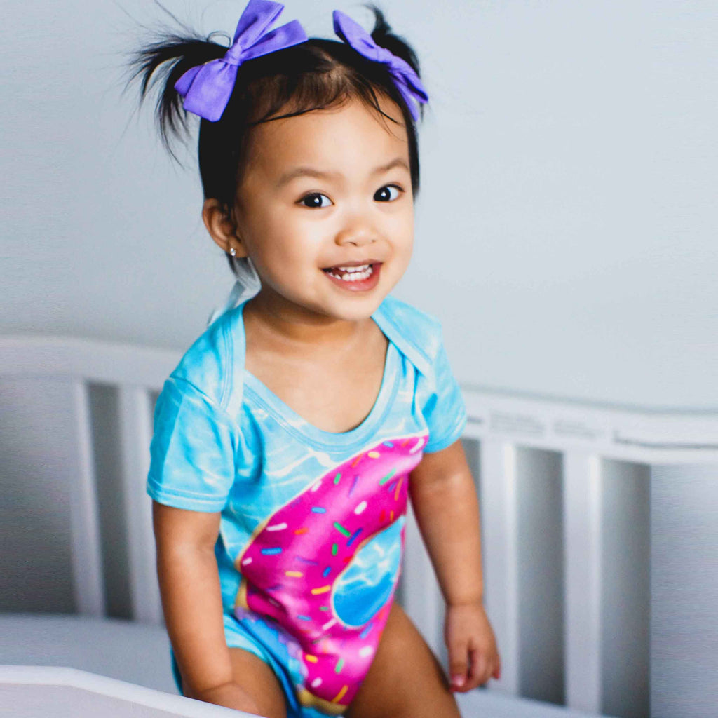 Baby wearing short sleeve bodysuit onesie printed with an image of an inflatable pool floatie shaped like a pink donut with sprinkles in a swimming pool