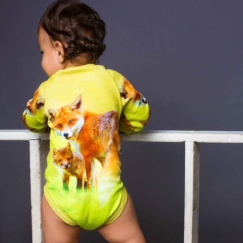 Baby wearing a raglan bodysuit with image of a fox and kit