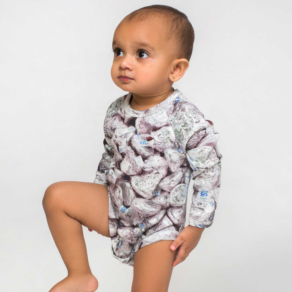 Baby wearing a raglan bodysuit onesie with all-over print of Hershey's Kisses chocolates