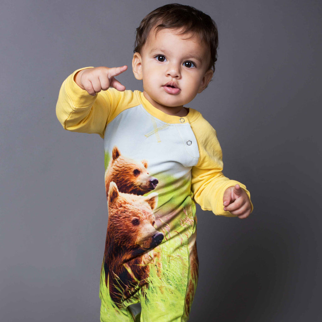 Baby wearing a raglan romper with image of mama bear and baby bear cub on her back in tall grass