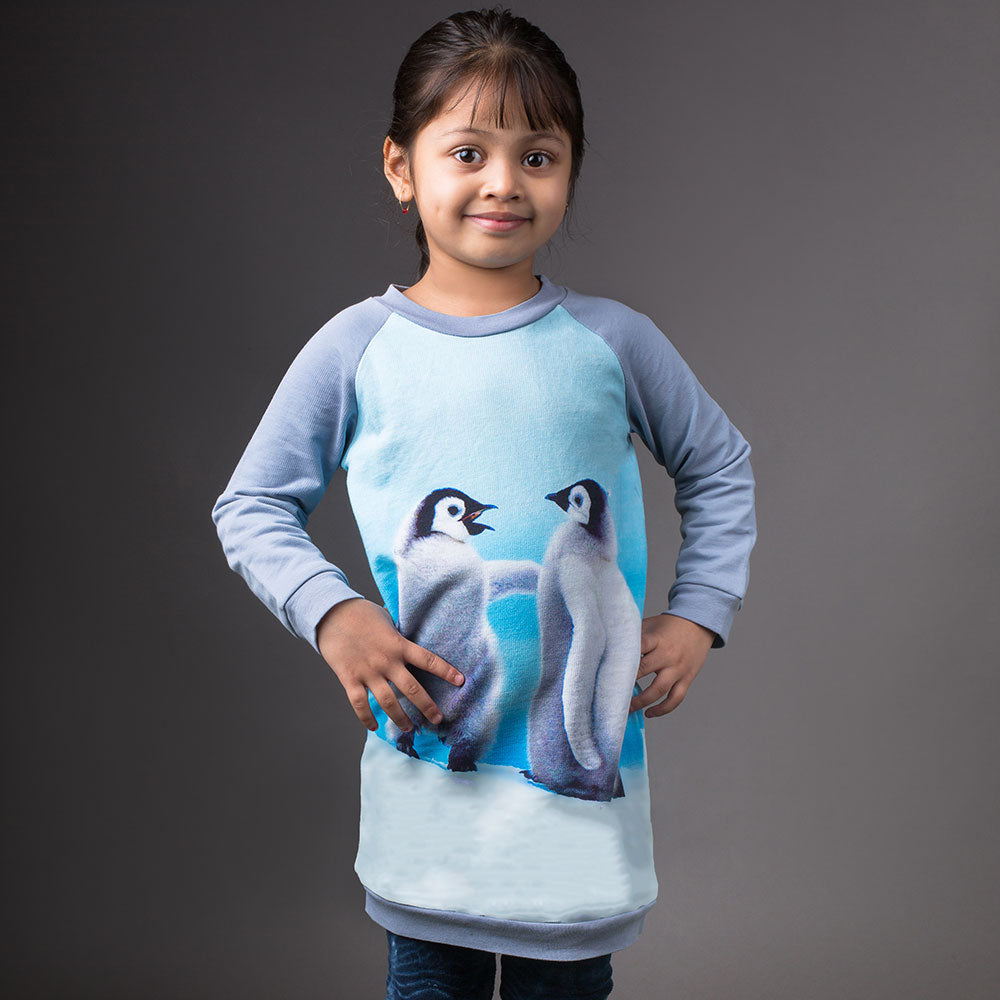 Girl wearing a raglan sweatshirt dress with image of two baby penguin chicks