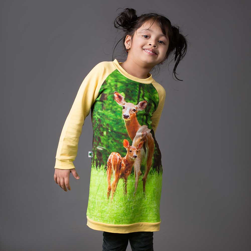 Girl wearing a raglan sweatshirt dress with image of a doe and fawn standing in a green field