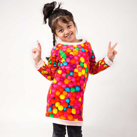 Girl wearing a raglan sweatshirt dress with overall print of multicoloured gumballs