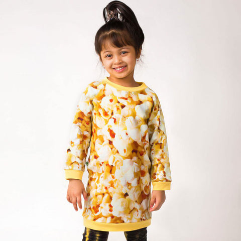 Girl wearing a raglan sweatshirt dress with all-over print of large scale popcorn