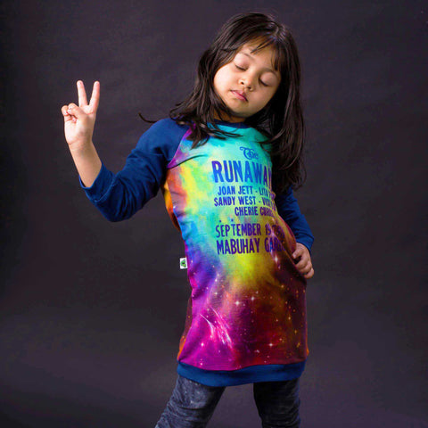 Girl wearing a raglan sweatshirt dress with image of vintage The Runaways concert flyer announcemement against a colourful star constellation background
