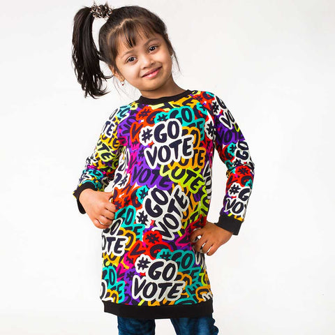 "Girl wearing a raglan sweatshirt dress with overall print of a stylized ""#GOVOTE"" motif"