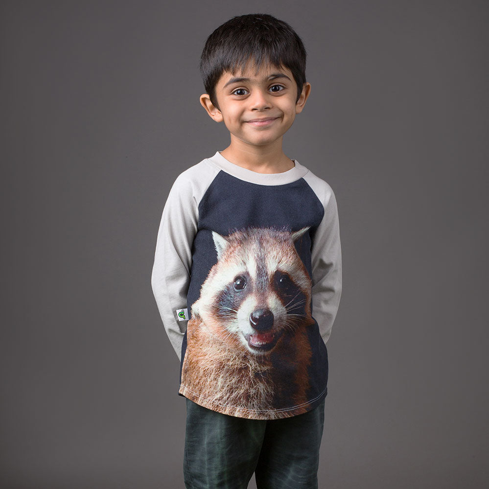 Boy wearing a raglan tee with image of a raccoon smiling