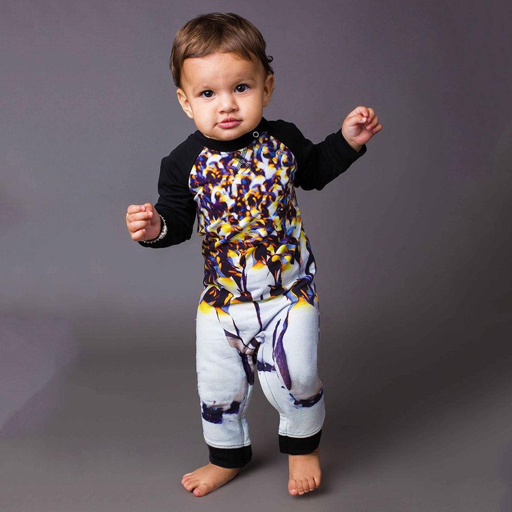 Baby wearing a raglan romper with image of a group of penguins