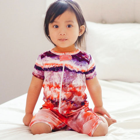 Toddler wearing a short sleeve shorts romper with large-scale, zoomed image of raw rose quartz crystal
