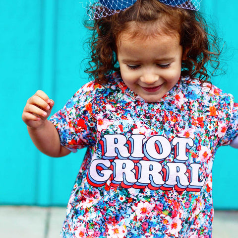 Girl wearing a boxy tee with an all-over print of flowers with the words Riot Grrrl across the front