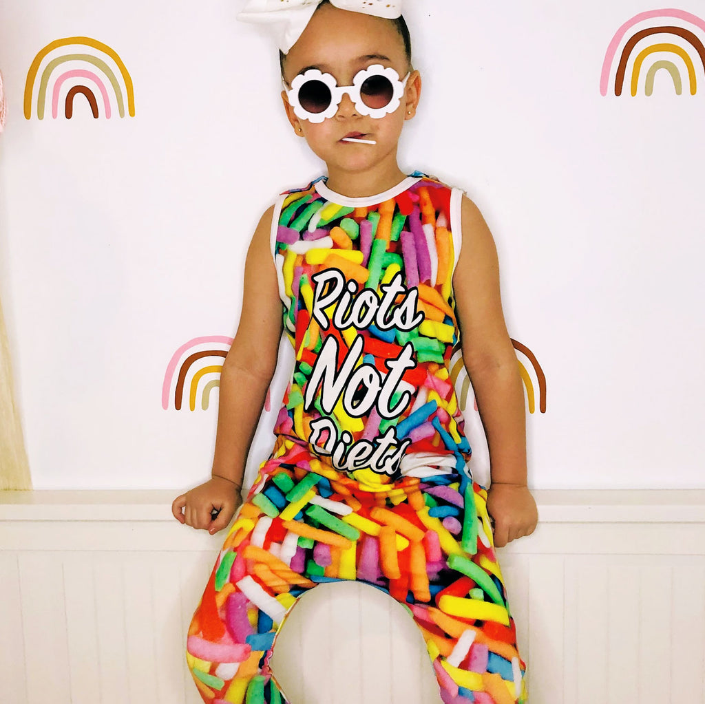 Girl wearing a jumpsuit with all-over print of oversized candy sprinkles and the words Riots Not Diets across the front body