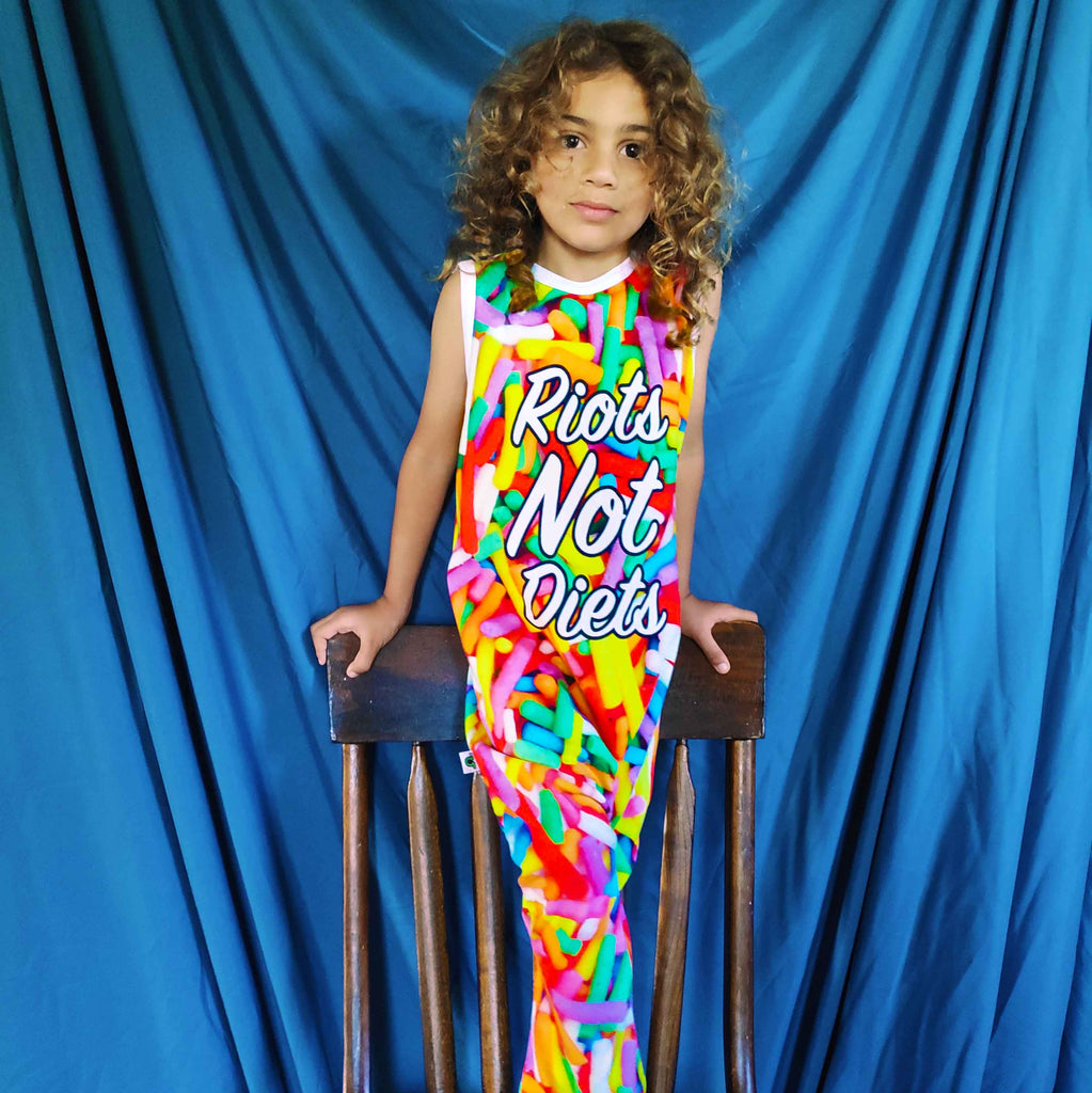 Boy wearing a jumpsuit with all-over print of oversized candy sprinkles and the words Riots Not Diets across the front body