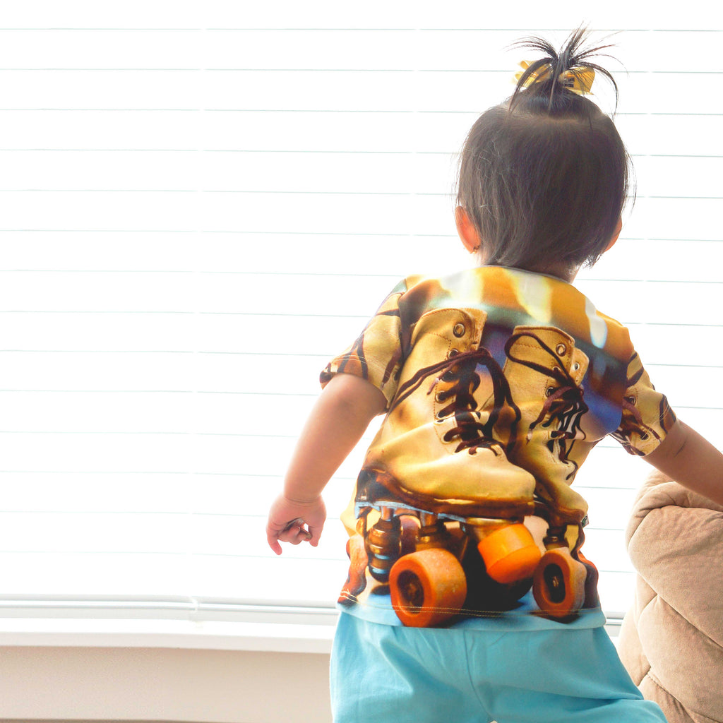 Toddler wearing a tee printed with an image of a pair of retro style roller skates paired with matching shorts