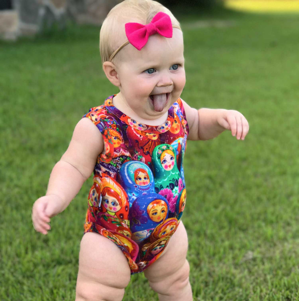 Baby wearing a tank bodysuit with an all-over print for Matryoshka or Russian nesting dolls