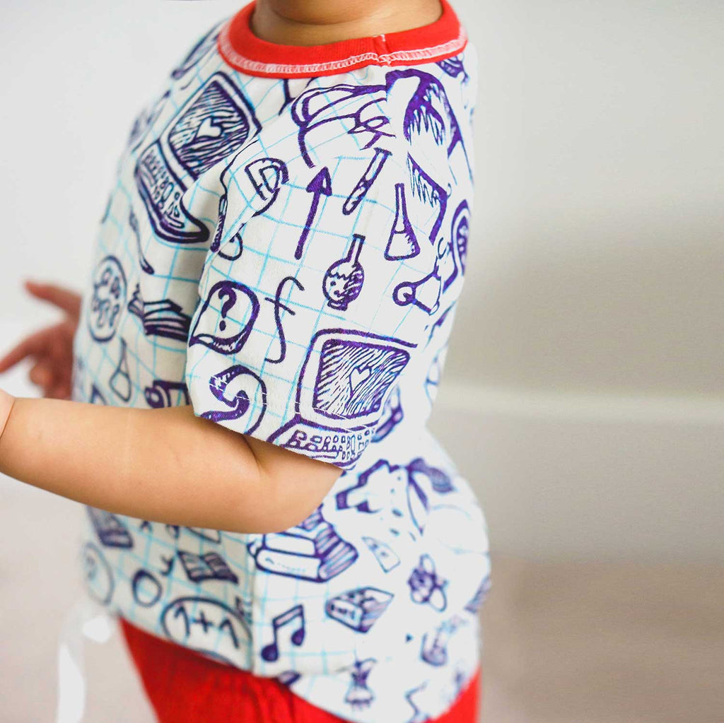 Toddler wearing a t-shirt printed with an image of school graph paper covered in hand-drawn doodles