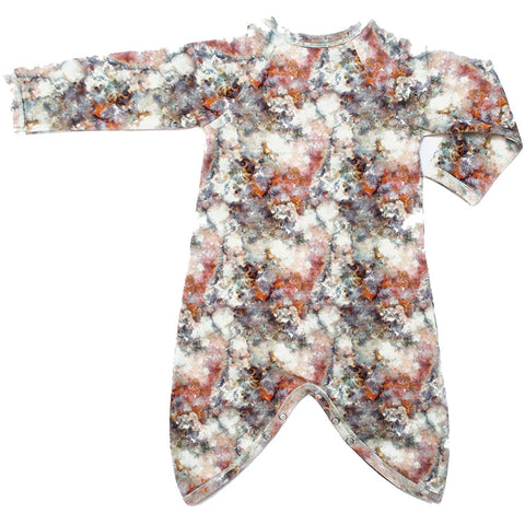 Back view of kimono wrap-front, drop-crotch romper with an all-over marble print