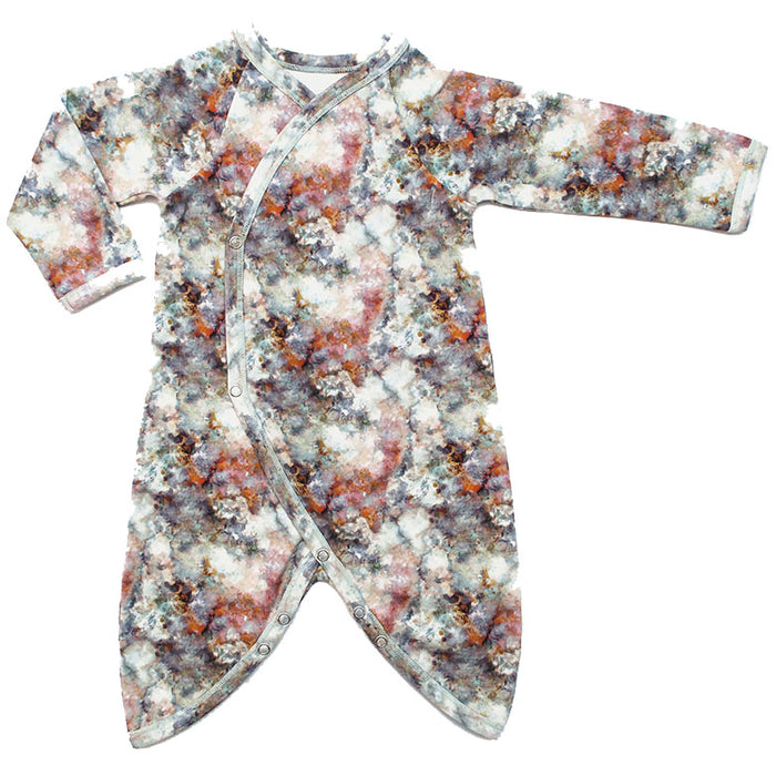 Front view of kimono wrap-front, drop-crotch romper with an all-over marble print