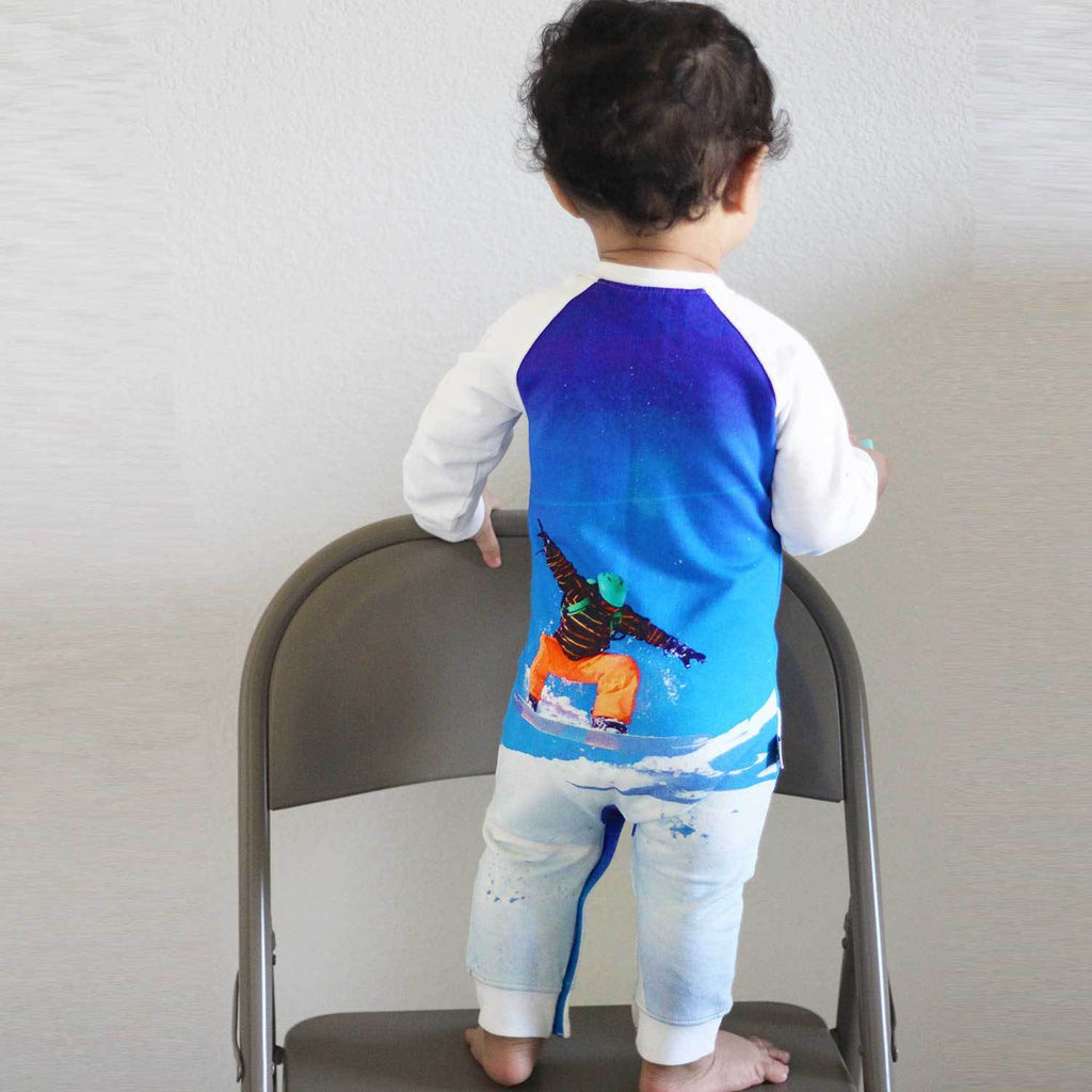 Toddler wearing a raglan romper printed with an image of a snowboarder catching air on a snowy hill