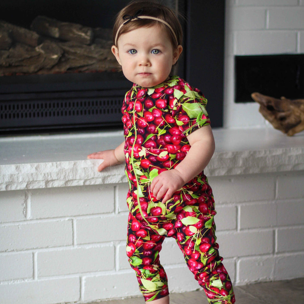 Baby wearing a short sleeve, full leg romper with all-over print of sour cherries